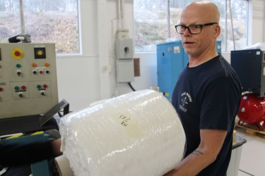 Pierre Larsson is carrying one of the large rolls of fluffy paper pulp which will be transformed into durable hangers.